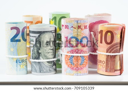 Currencies and money exchange trading concepts. The rolls of various currencies US Dollar, Euro and Chinese yuan banknotes with white rope band isolated on white background. #709105339