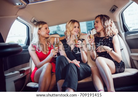 Pretty women having party in a limousine car and drinking champagne. #709191415