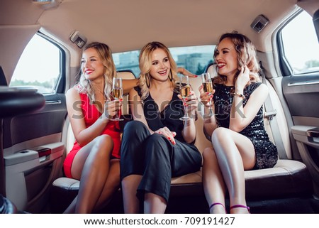 Pretty women having party in a limousine car and drinking champagne. #709191427