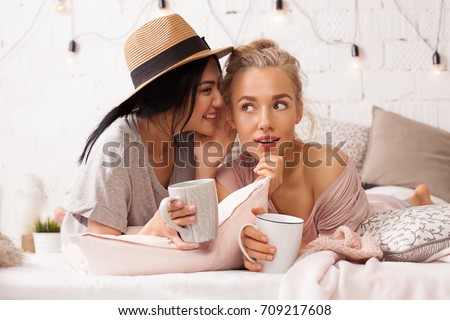 Young beautiful women communicate and tell each other secrets in the home interior over a cup of tea