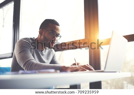 Concentrated dark skinned copywriter in eyewear typing text of publication for web site working on freelance, serious afro american student searching information for homework project in network #709235959