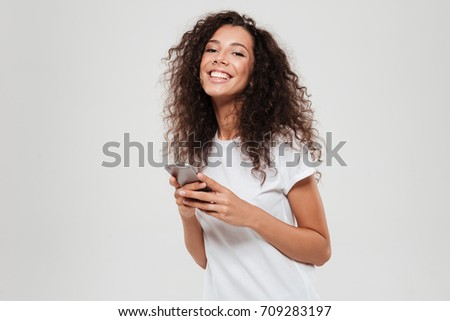 Smiling curly woman with smartphone in hands looking at the camera over gray background #709283197
