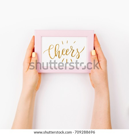 Woman holding  a photo frame. Beautiful spring mock up.  Easter concept.  Flat lay, top view