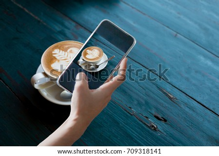 Hand holding mobile smart phone or cell telephone digital camera taking photo to Cup of Hot Cappuccino coffee with fresh milk Art's surface floating on top for Post upload file to online on Internet .