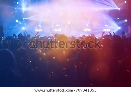 Crowd at concert - Cheering crowd in front of bright colorful stage lights #709341355