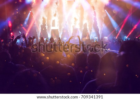 Crowd at concert - Cheering crowd in front of bright colorful stage lights #709341391