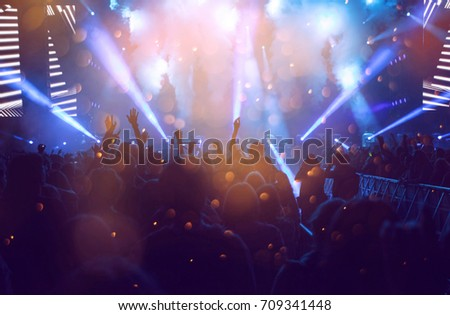 Crowd at concert - Cheering crowd in front of bright colorful stage lights #709341448
