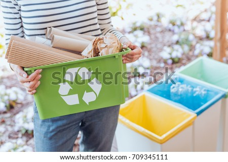 Activist taking care of environment, sorting paper waste to proper recycling bin on terrace Royalty-Free Stock Photo #709345111