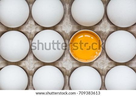 Chicken egg is half broken among other eggs Royalty-Free Stock Photo #709383613