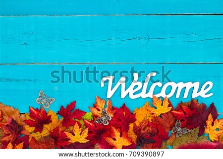 Welcome sign with colorful fall leaves border and antique rustic teal blue wood background; autumn, Thanksgiving, Halloween, seasonal nature sign with painted wooden copy space