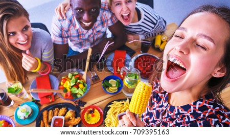 People with drinks while sitting at the dining table #709395163