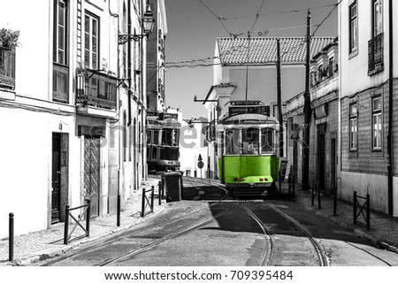 Green tram on old streets of Lisbon, Portugal, popular touristic attraction, and destination. Black and white picture with a coloured tramway.