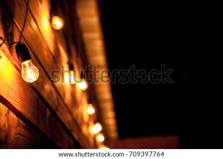 Burning garlands garland on a wooden background. Light bulbs on wooden background. Evening Wooden Stage In The Garden With Lamps For Parties Or Wedding #709397764