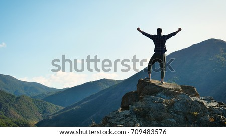 On the edge of a rocky cliff a man raises his hands to heaven as a sign of freedom or victory and in the background a fantastic landscape. Concept of: breathing, freedom, journey, life, love. Royalty-Free Stock Photo #709483576