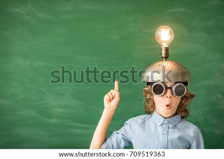 Portrait of child in classroom. Child with toy virtual reality headset in class. Success, idea and innovation technology concept. Back to school. Kid against blackboard with copy space Royalty-Free Stock Photo #709519363