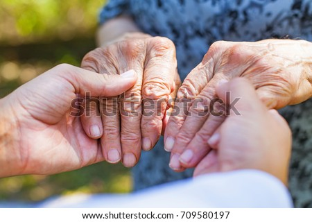 Close up medical doctor holding senior woman's shaking hands, Parkinson disease #709580197