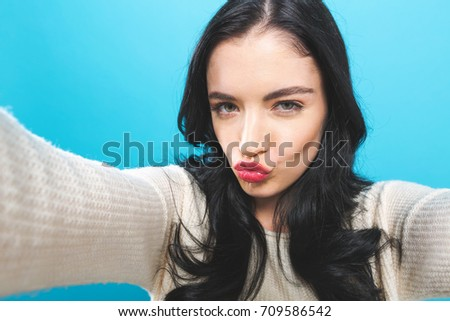 Young woman taking a selfie on a blue background #709586542