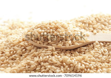 Brown rice or not peeled rice in a wooden spoon. Cereals background.  #709614196
