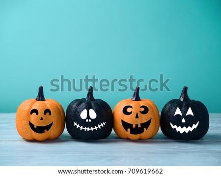 Halloween glitter pumpkin jack o lantern decor with funny faces.  Royalty-Free Stock Photo #709619662
