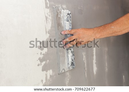 Closeup of repairman hand plastering a wall with putty knife or spatula  #709622677