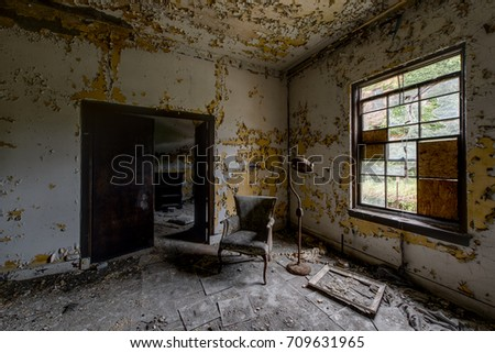 Inside a patient room with some furniture in a long abandoned hospital and nursing home. #709631965