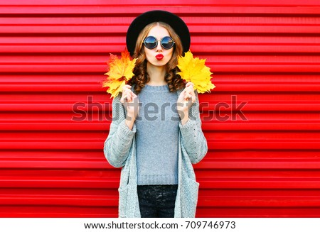 Fashion autumn portrait woman with yellow maple leaves on a red background #709746973