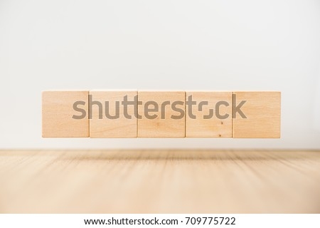 Business concept - Abstract geometric real floating wooden cube on grey background and it's not 3D render, float on wood floor white background for display or montage word.
