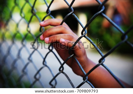 Hand in jail with girl and house of detention concept, vignette effect and selective focus. Royalty-Free Stock Photo #709809793