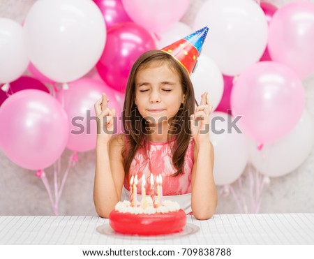 Girl in the birthday hat with a cake with candles makes a wish with his fingers crossed