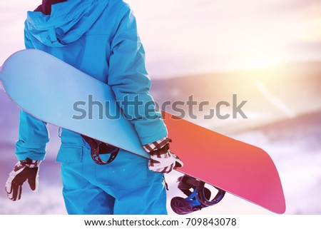 Woman holding snowboard in hands. Closeup view. Snowboarder or snowboarding concept at sunrise or sunset time #709843078