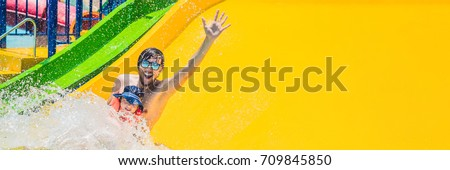 Father and son on a water slide in the water park. Long Format.