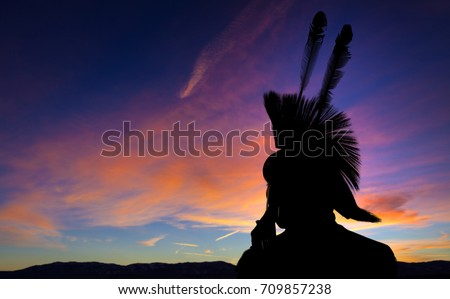 Native American Indian wearing head dress in silhouette against sunset background.