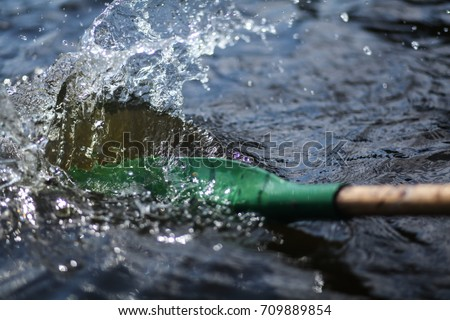boat oar in the water and splashing water Royalty-Free Stock Photo #709889854