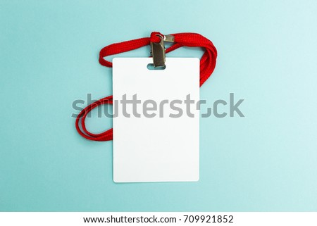 Blank badge mockup isolated on blue background. Plain empty name tag mock up with red string. #709921852