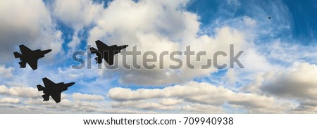 Silhouettes of three F-35 aircraft against the blue sky and white clouds #709940938