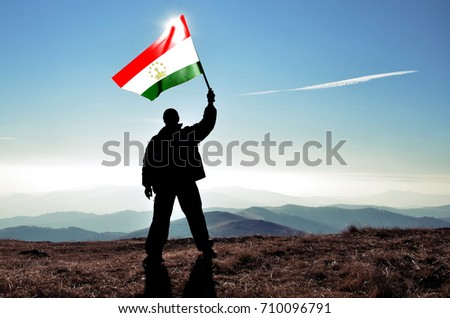 Successful silhouette man winner waving Tajikistan flag on top of the mountain peak #710096791
