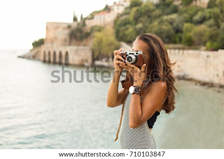 Travelling brunette woman wearing stripe black and white dress and large watch photographing shooting with vintage film camera against blurred background of Alanya castle wall and medieval shipyard. #710103847