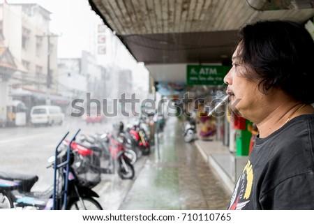 ChiangRai THAILAND - September: 5: 2017: Tourist were smoking In The Landmark Street on heavy rain ChiangRai Thailand. #710110765