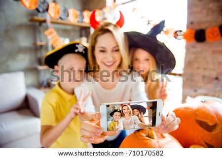 Kids say cheers! Dressed in spooky halloween costumes headwear mum and her cheerful kids are bonding embracing, lady is taking selfie, making memories, siblings gesturing, creepy decorations