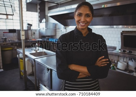 Portrait of smiling young waitress standing in cafe #710184409