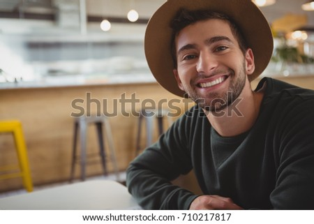 Portrait of smiling young man sitting in cafe #710217817