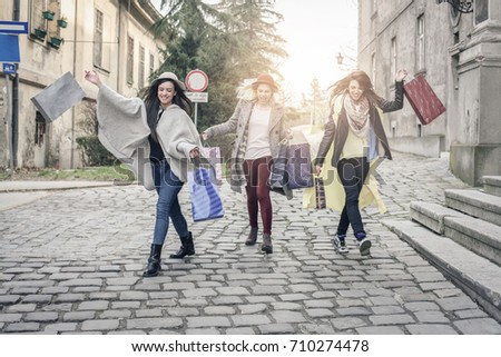 Three best friends running  on the street . Young females best friends doing shopping on the streets. #710274478