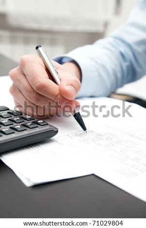 Closeup of a businessman's hands while writing some documents #71029804
