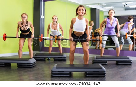 Portrait of happy cheerful  women exercising with barbell in fitness club #710341147