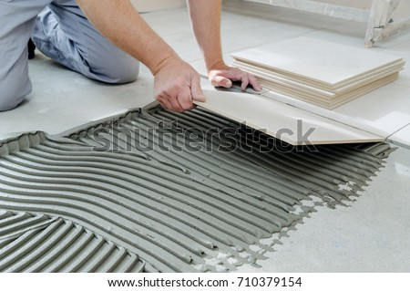 The hands of the tiler are laying  the ceramic tile on the floor. Royalty-Free Stock Photo #710379154