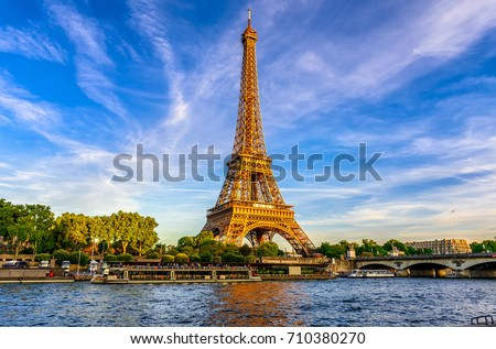 Paris Eiffel Tower and river Seine at sunset in Paris, France. Eiffel Tower is one of the most iconic landmarks of Paris. Royalty-Free Stock Photo #710380270