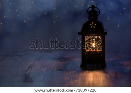 Lantern with candles and gold stars on a blue background. Beautiful background for the Christmas holidays #710397220