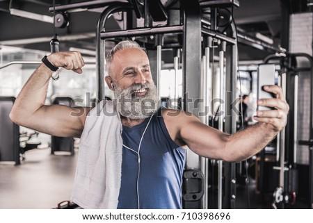 Joyful senior male making picture of himself in modern gym