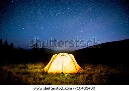 Glowing camping tent in the night mountain forest under a starry sky #710481430