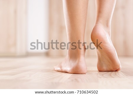 Flat feet. Healthy foot baby.  Feet of baby's naked against the background of the wooden floor  #710634502